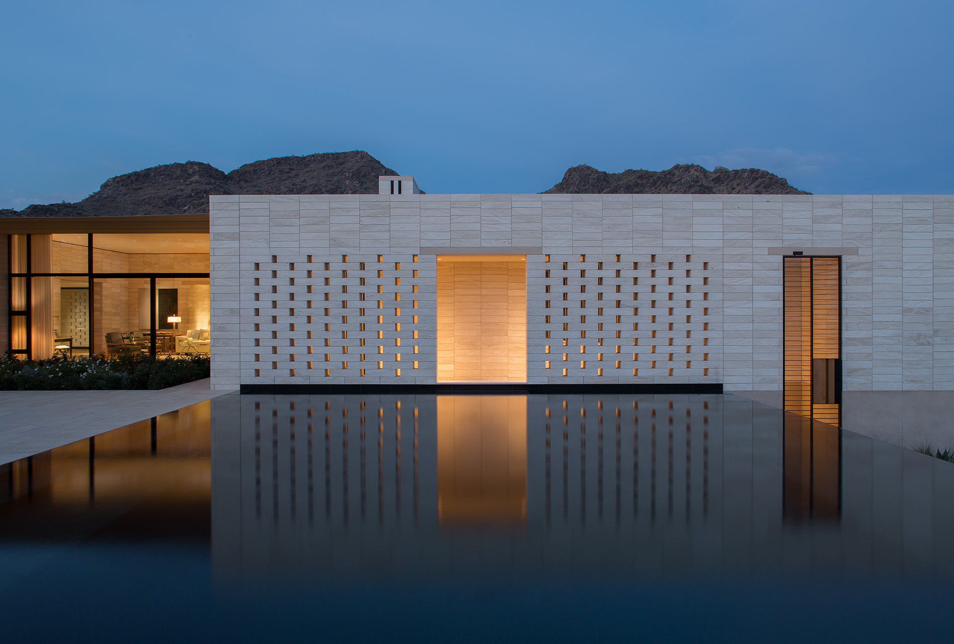 View of the stone villa by night with illuminated galvanized sliding panels