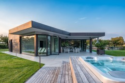 External view of the pool house with with motorized lift and slide doors and wide burnished brass fenestration